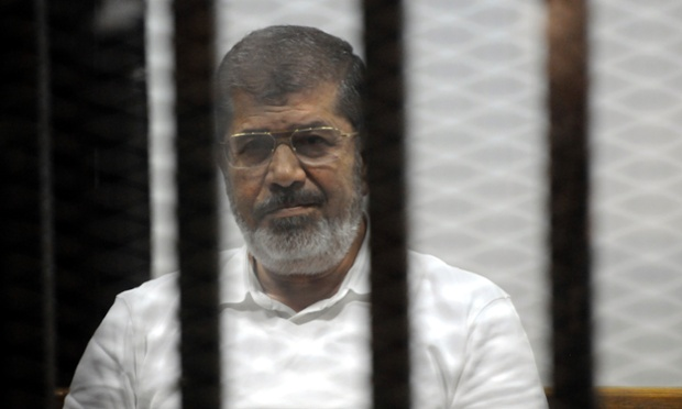 Egypt's ousted Islamist President Mohammed Morsi sits in the defendant cage in the Police Academy courthouse during a court hearing on charges of inciting the murder of his opponents, in Cairo, Egypt, Monday, Nov. 3, 2014. Morsi is charged with conspiring with foreign groups, inciting the murder of his opponents, orchestrating prison breaks during the 2011 uprising that toppled his predecessor, Hosni Mubarak, and leaking secret documents to Qatar via the Doha-based Al-Jazeera broadcaster. (AP Photo/Mohammed al-Law)