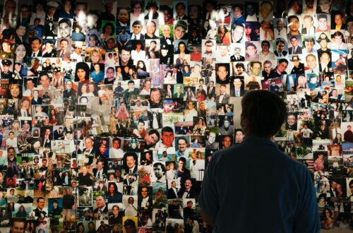 A survivor of the 9/11 attacks on the World Trade Center looks at photos of those who perished, in a display at the 9/11 Tribute Museum, Aug. 6, in New York. — Mark Lennihan, Associated Press